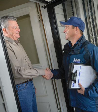Len The Plumber technician smiling and shaking a Baltimore customer's hand in a doorway.
