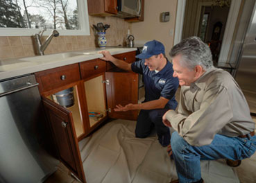 Uniformed plumber speaking with a customer about garbage disposal repairs and looking under their kitchen sink