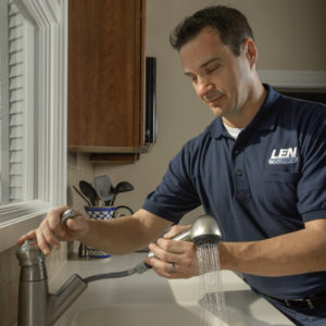Len The Plumber technician testing pull-out spray head on a kitchen faucet in the DC area.