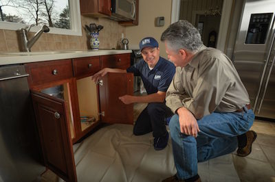 Len the Plumber technician and Philadelphia homeowner area kneeling and talking in front of sink.