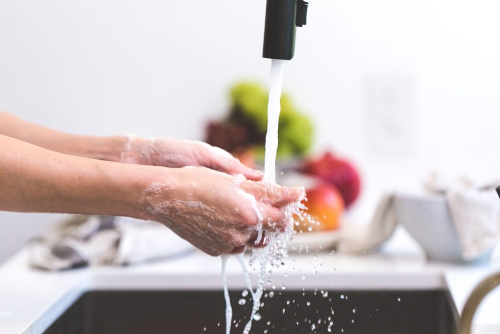 Person washing hands in sink using new faucet