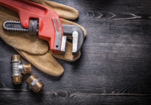 Plumbing gloves, pipe wrench, and fittings laying on wooden floor.