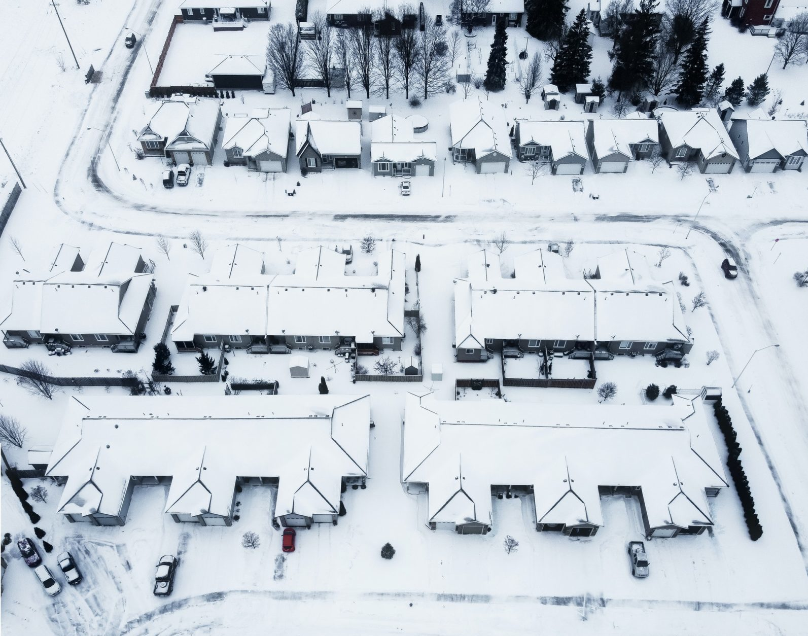 Aerial view of snow-covered houses in suburban neighborhood.