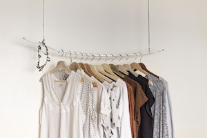 Clothes on hangers arranged on suspended bar.
