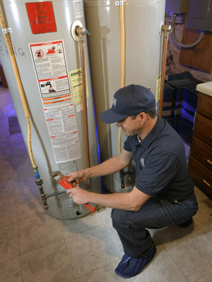 Len The Plumber technician kneeling and preparing to make water heater repairs in a DMV Metro home.