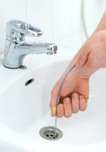 hands using a plumbing snake to repair clogged drain