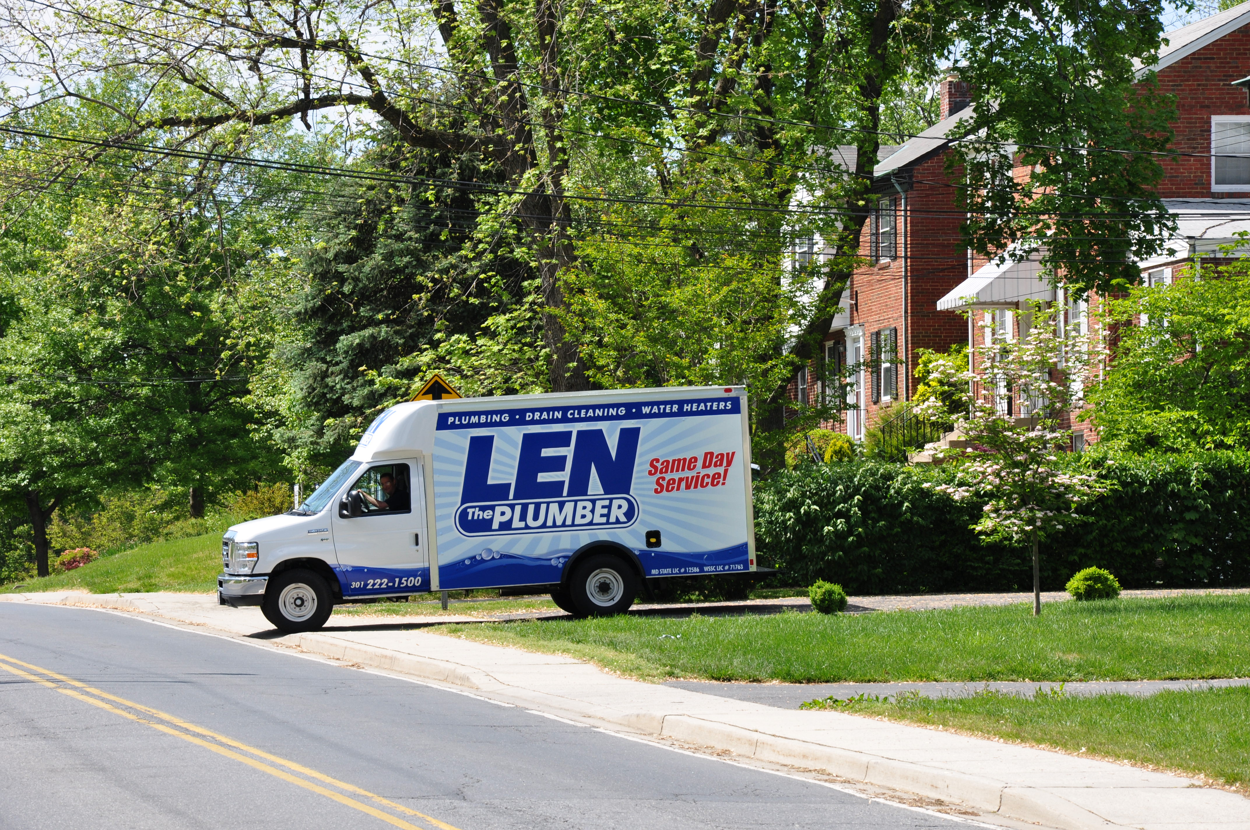 Len The Plumber commercial truck pulling out of a homeowner's driveway in the DMV Metro area.