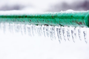 Frozen pipe covered in icicles