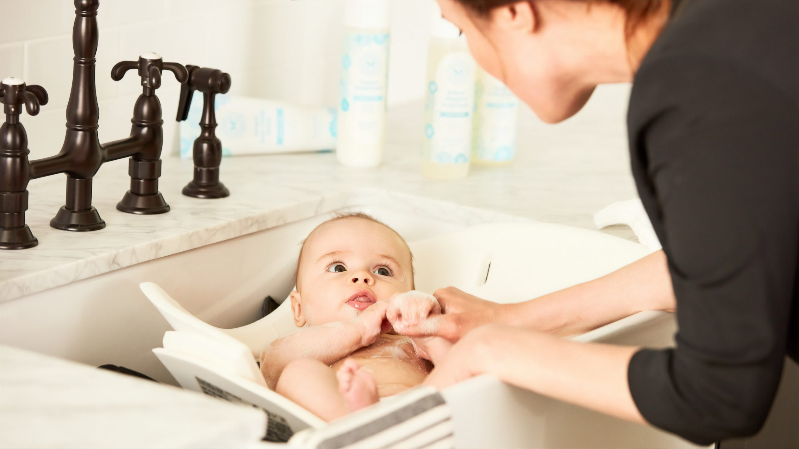 Mother washing baby in sink